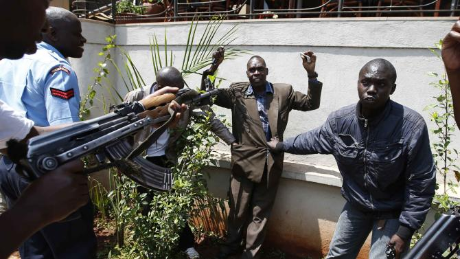 Policemen search a man for weapons as he walked out of Westgate Shopping Centre in Nairobi