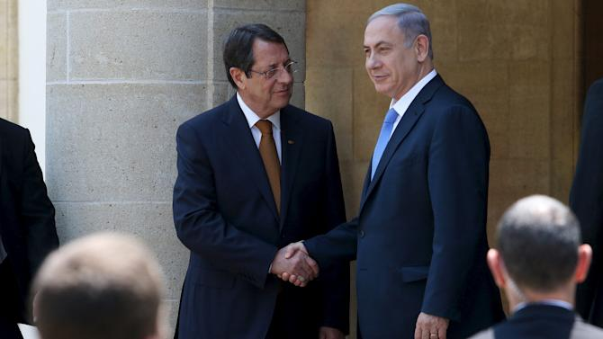 Israel's Prime Minister Netanyahu shake hands with Cyprus' President Anastasiades while security guards look on during a welcome ceremony at the presidential palace in Nicosia