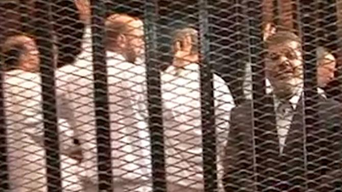 FILE - This Monday, Nov. 4, 2013 file image made from video provided by Egypt's Interior Ministry shows ousted President Mohammed Morsi, right, speaking from the defendant's cage as he stands with co-defendants in a makeshift courtroom during a trial hearing in Cairo, Egypt. Morsi had his first extensive meeting with lawyers, Tuesday, Nov. 12, 2013, consulting in prison with a team from his Muslim Brotherhood over his ongoing trial on charges of inciting murder. So far, Morsi is refusing to accept any legal representation in the trial, insisting he remains president, and his son says he wants to take legal action against those prosecuting him after his ouster by the military.(AP Photo/Egyptian Interior Ministry, File)