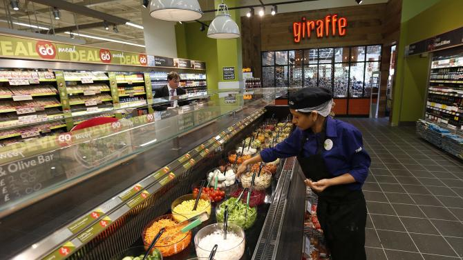 A Tesco employee prepares the salad bar outside the Giraffe restaurant at a Tesco Extra supermarket in Watford, north of London