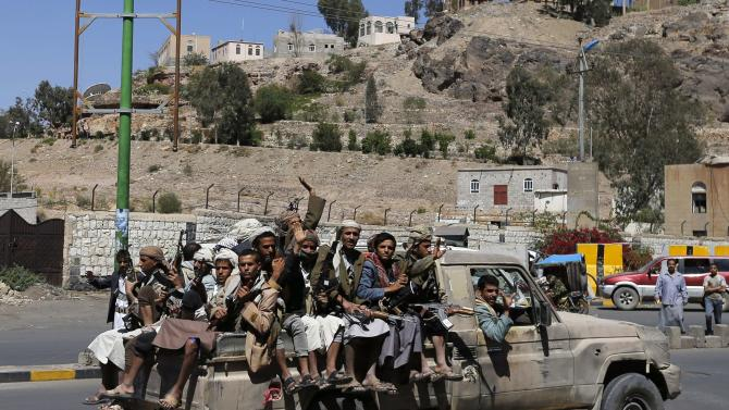 Shi'ite rebels ride on a truck outside the state television compound in Sanaa