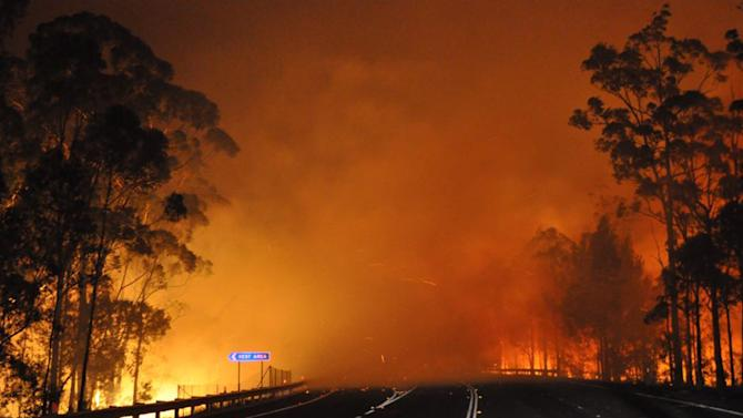 In this photo provided by the New South Wales Rural Fire Service a wildfire near Deans Gap, Australia, crosses the Princes Highway Tuesday, Jan. 8, 2013. Firefighters are battling scores of wildfires in southeastern Australia as authorities evacuate national parks and warned that hot, dry and windy conditions were combining to raise the threat to its highest alert level. (AP Photo/NSW Rural Fire Service, James Morris)