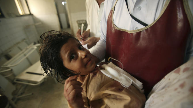 A member of the hospital staff carries a child injured in an attack, at a local hospital in Peshawar, Pakistan on Tuesday, Sept 13, 2011. Gunmen attacked a school van in northwestern Pakistan killing three children, the driver and police said. (AP Photo/Mohammad Sajjad)