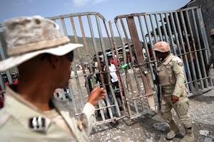 Dominican soldiers control access at the Haitian-Dominican…
