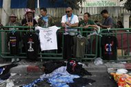 A man displays a shirt damaged in an explosion near Victory Monument in Bangkok January 19, 2014. REUTERS/Paul Barker
