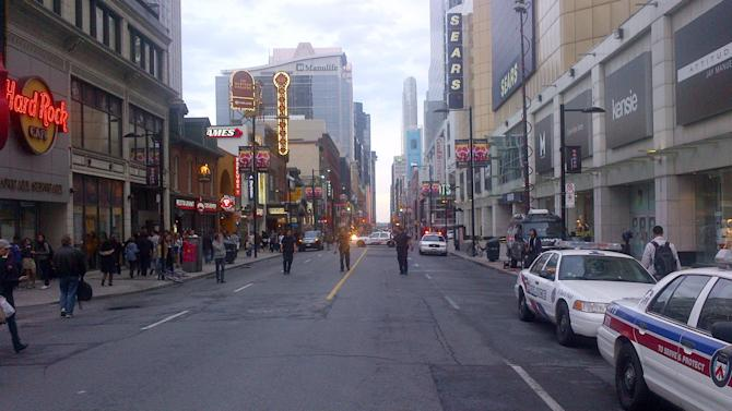 Police walk up Yonge Street outside the Eaton Centre shopping mall in Toronto, Saturday, June 2, 2012. Shots were fired at Toronto's downtown Eaton's Centre Saturday evening.(AP Photo/The Canadian Press, John Chidley-Hill)