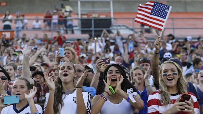 FILE - In this Nov. 10, 2013, file photo, fans cheer during the first half of an international friendly soccer match between the U.S. and Brazil women's national teams in Orlando, Fla. A year after the World Cup transformed millions of Americans into red-white-and-blue-wearing soccer fanatics, another chance to cheer for a national team will arrive. Not just in group-stage matches, but very possibly for a championship. The Women's World Cup kicks off in Canada in June 2015 _ and if the favored U.S. squad advances far, expect some more massive TV audiences. (AP Photo/John Raoux, File)