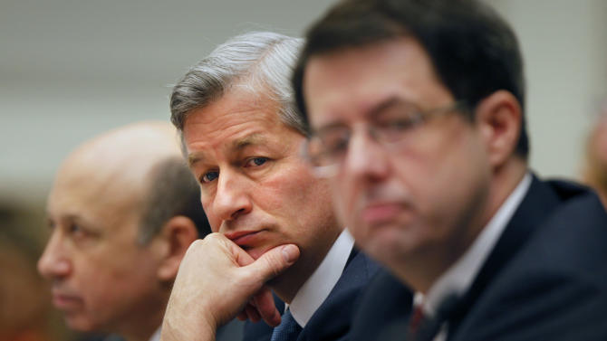 """FILE - In this Feb. 11, 2009 file photo, JPMorgan Chase & Co. Chief Executive Officer Jamie Dimon, center, flanked by Goldman Sachs & Co. Chief Executive Officer and Chairman Lloyd C. Blankfein, left, and Bank of New York Mellon Chairman Chief Executive Officer Robert Kelly, are seen on Capitol Hill in Washington during a House Financial Services Committee hearing. Dimon had to face stock analysts and reporters on Thursday, May 10, 2012, and confess to a """"flawed, complex, poorly reviewed, poorly executed and poorly monitored"""" trading strategy that lost a surprise $2 billion. (AP Photo/Lawrence Jackson, File)"""