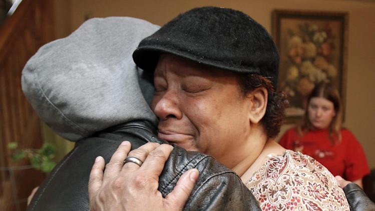 Lisa Williamson, mother of Brandon A. Murray, hugs her son's friend Monday, March 11, 2013, in Warren, Ohio. Investigators spent Monday trying to piece together why eight teenagers were crammed into a speeding SUV without the owner's permission when it flipped over into a pond, killing six of them, including Murray. (AP Photo/Tony Dejak)
