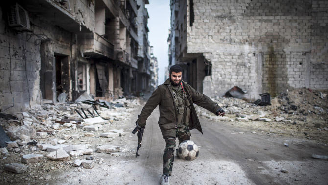 """A Syrian rebel plays football in the Saif al-Dawlah neighborhood of Aleppo, Syria, Wednesday, Jan. 2, 2013. The United Nations estimated Wednesday that more than 60,000 people have been killed in Syria's 21-month-old uprising against authoritarian rule, a toll one-third higher than what anti-regime activists had counted. The U.N. human rights chief called the toll """"truly shocking."""" (AP Photo/Andoni Lubacki)"""