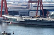 China's first aircraft carrier is berthed at Dalian port on September 5. China's first aircraft carrier has been handed over to the navy of the People's Liberation Army, state press said, amid rising tensions over disputed waters in the East and South China Seas