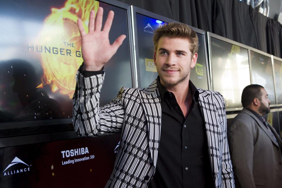 "Liam Hemsworth, who portrays Gale Hawthorne, waves to fans as he arrives on the red carpet for the premier the film ""The Hunger Games"" on Monday March 19, 2012 in Toronto. (AP Photo/The Canadian Press, Chris Young)"