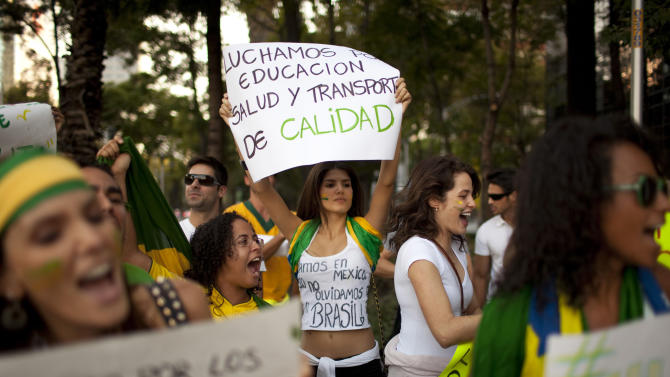 """Dianine Nunes holds a banner that reads in Spanish; """"We are fighting for quality in education, heath and transport,"""" during a protest near the Angel of Independence monument in Mexico City, Tuesday, June 18, 2013. Brazilian nationals gathered to condemn the heavy tax burden in Brazil, corrupt politicians and woeful public education, health and transport systems as the nation hosts the Confederations Cup soccer tournament and prepares for next month's papal visit.(AP Photo/Ivan Pierre Aguirre)"""