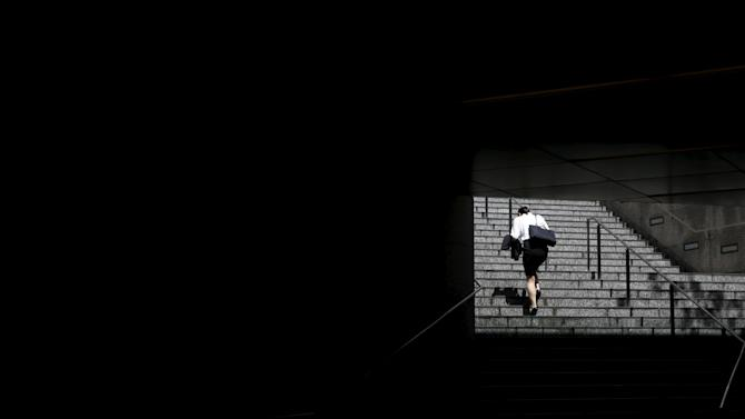 Woman walks up the stairs from the underpass of an office building in Tokyo