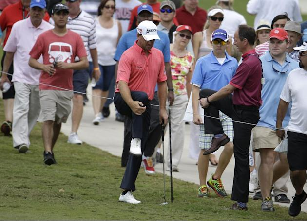 Graham McDowell of Northern Ireland, left, stretches as he consults with an official during the final round of the Cadillac Championship golf tournament Sunday, March 9, 2014, in Doral, Fla. (AP Photo
