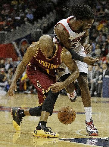 Cleveland Cavaliers point guard Jarrett Jack (1) and Atlanta Hawks small forward DeMarre Carroll (5) collide as they chase a loose ball in the second half of an NBA basketball game Friday, Dec. 6, 201