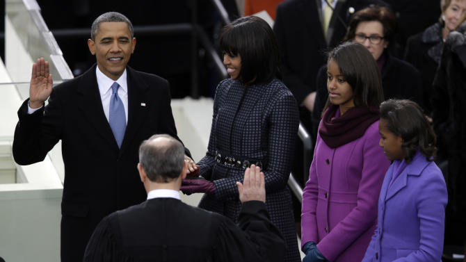 President Barack Obama receives the oath of office from Chief Justice John Roberts as first lady Michelle Obama (L-R) and his daughters Malia and Sasha listen at the ceremonial swearing-in at the U.S. Capitol during the 57th Presidential Inauguration in Washington, Monday, Jan. 21, 2013. (AP Photo/Evan Vucci)