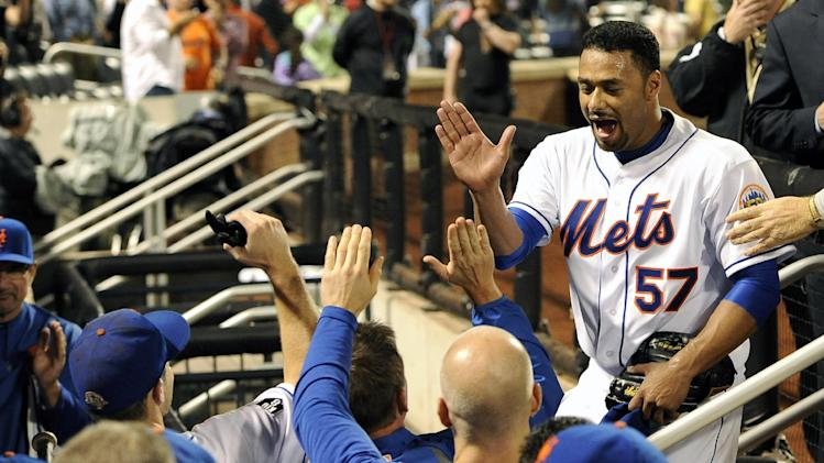 New York Mets starting pitcher Johan Santana (57) high-fives teammates at the dugout after throwing a no-hitter against the St. Louis Cardinals in a baseball game on Friday, June 1, 2012, at Citi Field in New York. The Mets won 8-0. (AP Photo/Kathy Kmonicek)