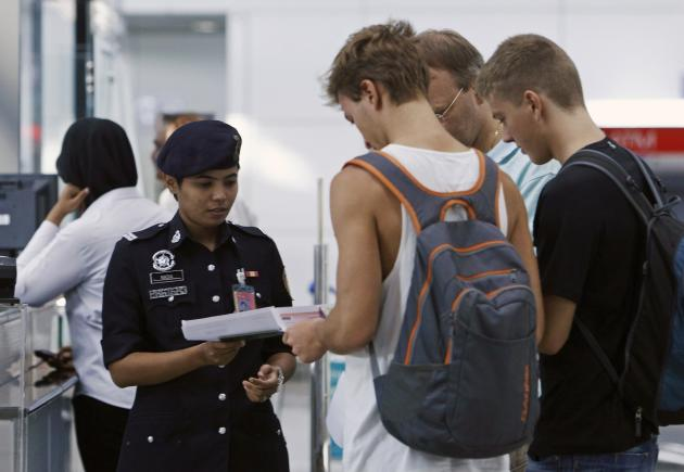 A customs officer checks the travel documents and passports of passengers at Kuala Lumpur International Airport