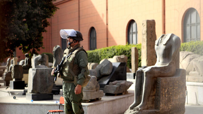 An Egyptian army soldier stands guard near antiquities of the Egyptian museum in Cairo, Egypt, Saturday, Jan. 29, 2011. Hundreds of anti-government protesters returned Saturday to the streets of central Cairo, chanting slogans against Hosni Mubarak and attacking police just hours after the Egyptian president fired his Cabinet and promised reforms but refused to step down. (AP Photo/Amr Nabil)