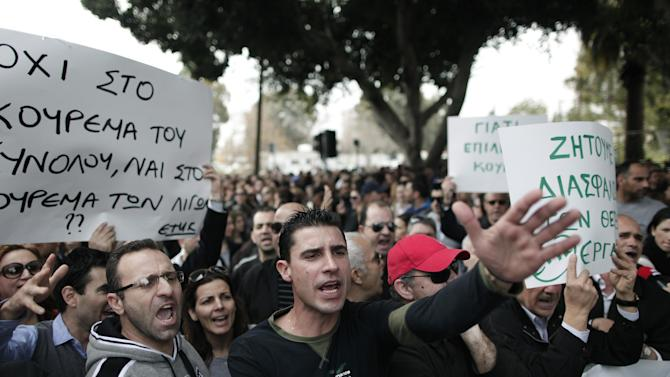 """Protesting employees of Laiki bank chant slogans outside the Cypriot parliament, Friday, March 22, 2013. Cypriot authorities were putting the final touches Friday to a plan they hope will convince international lenders to provide the money the country urgently needs to avoid bankruptcy within days. """"The next few hours will determine the future of this country,"""" said government spokesman Christos Stylianides.(AP Photo/Petros Giannakouris)"""