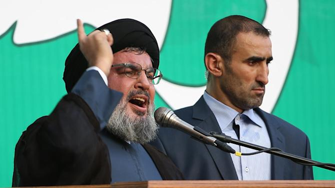 "Hezbollah leader Sheik Hassan Nasrallah, left, speaks to a crowd of tens of thousands of supporters, not shown, during a rally denouncing an anti-Islam film that has provoked a week of unrest in Muslim countries worldwide, in the southern suburb of Beirut, Lebanon, Monday Sept. 17, 2012. Nasrallah who does not usually appear in public for fear of assassination called for Monday's protests in Beirut, saying the U.S. must be held accountable for the film because it was produced in America. Arabic reads, ""the messenger of God."" (AP Photo/Hussein Malla)"