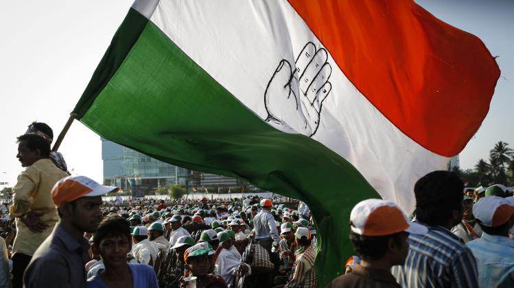Supporters of India's ruling Congress party holding a huge party flag attend an election campaign rally in Mumbai