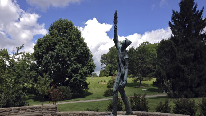 In this July 16, 2014 photo, a memorial to John Chapman, better known as American folklore hero Johnny Appleseed, stands in Spring Grove Cemetery in Cincinnati. An educational center and museum in Urbana dedicated to the life and works of the man credited with introducing many apple orchards in Ohio and surrounding states, has received an anonymous donation to help finance a traveling exhibit that will tell the story of the man behind the legend. (AP Photo\Lisa Cornwell)