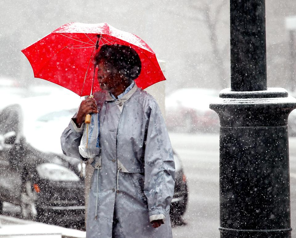 A woman waits for the light to change at a cross walk in the snow in downtown Denver on Wednesday, May 1, 2013. The Denver area could get up to around 5 inches, but not much is sticking to the pavement, still warm after a weekend with temperatures in the 70s. (AP Photo/Ed Andrieski)