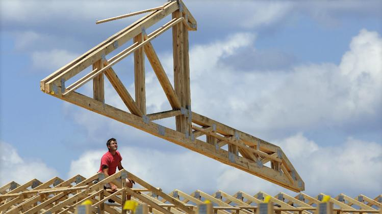 In this July 17, 2014 photo, construction workers build a commercial complex in Springfield, Ill. The government issues its first of three estimates of how fast the U.S. economy grew in the April-June quarter on Wednesday, July 30, 2014. (AP Photo/Seth Perlman)
