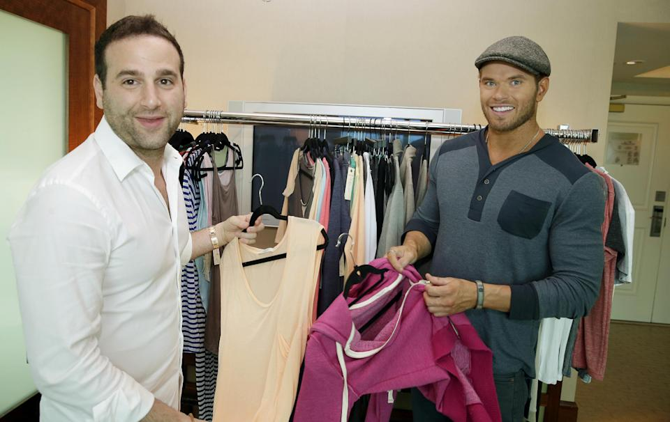 Actor-designer Kellan Lutz, right, and his partner Danny Guez look through their pre-spring 2014 clothing line Abbot + Main at the Mandalay Bay Hotel on Monday, Aug. 19, 2013 in Las Vegas. (Photo by Isaac Brekken/Invision/AP)