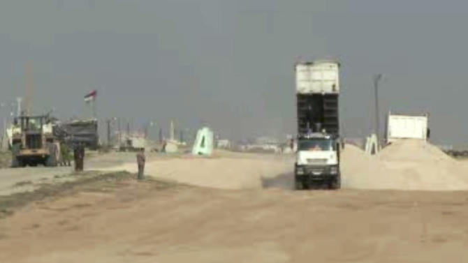 In this frame grab taken from AP video, trucks unload gravel brought in from Egypt at the Rafah border crossing in the southern Gaza Strip Monday, Dec. 31, 2012. Israel has started allowing long-banned building materials into the Gaza Strip, its first key concession to the territory's Hamas rulers under a cease-fire that ended eight days of intense fighting in November, the military said Monday. (AP Photos/APTN)