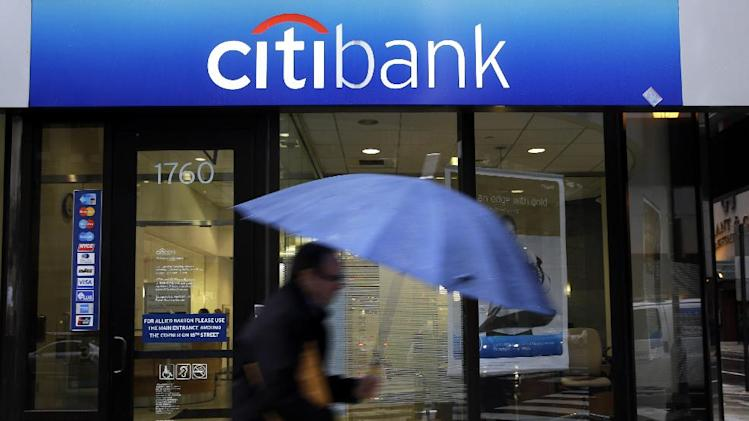 FILE - In this Tuesday, Jan. 14, 2014, file photo, a person walks past a Citibank location, in Philadelphia. As announced Thursday, March 20, 2014,a ll but one of the nation's 30 largest banks are in a stronger position to withstand a severe U.S. recession and a global downturn than at any time since the financial crisis, the Federal Reserve has determined .(AP Photo/Matt Rourke)