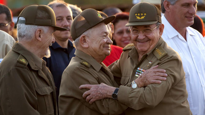 Cuba's President Raul Castro, right, embraces Commanders of the Revolution Guillermo Garcia Frias, center, and Ramiro Valdez, left, at an event celebrating Revolution Day in Guantanamo, Cuba, Thursday, July 26, 2012. Cuba marks the 59th anniversary of the July 26, 1953 rebel attack led by Fidel and Raul Castro on the Moncada military barracks. The attack is considered the beginning of the revolution that culminated with dictator Fulgencio Batista's ouster. (AP Photo/Ramon Espinosa)