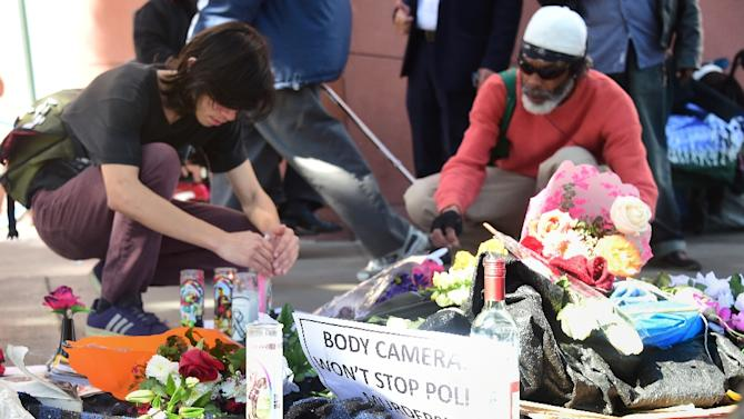 "People pay their respects at an ever-growing makeshift memorial in Los Angeles, California on March 3, 2015 where a homeless man known as ""Africa"" was shot and killed over the weekend"