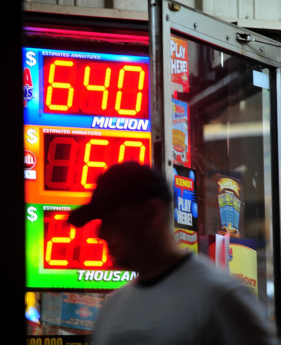 A customer walks out of the Riverside Travel Center in Hilton, Ga., late Friday night after purchasing a lottery ticket for the Mega Millions Lottery which reached an estimated jackpot of $645 million for Friday night's drawing. (AP Photo/Jay Hare, The Eagle)