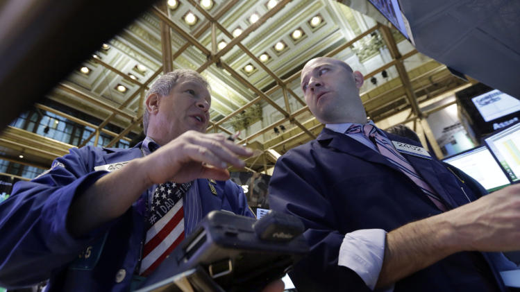 Trader Richard Newman, left, and specialist Jay Woods work on the floor of the New York Stock Exchange Friday, Dec. 6, 2013. The stock market is up sharply after the U.S. government reported a big increase in hiring last month. (AP Photo/Richard Drew)