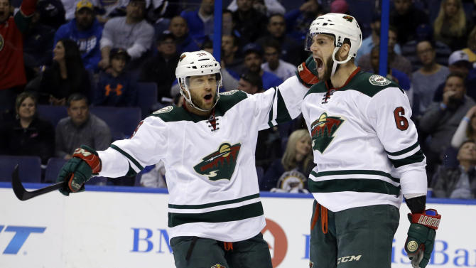 Minnesota Wild's Marco Scandella, right, is congratulated by teammate Jason Pominville after scoring during the first period in Game 5 of an NHL hockey first-round playoff series against the St. Louis Blues, Friday, April 24, 2015, in St. Louis. (AP Photo/Jeff Roberson)
