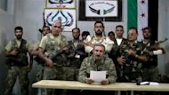 Free Syrian Army (FSA) chief Riad al-Asaad (C) is seen speaking from a secret location in Syria in a video uploaded to YouTube. Rebels have moved their command base from Turkey to &quot;liberated areas&quot; inside Syria, they announced on Saturday as regime troops and rebels battled for control of a corridor near the border and in Aleppo city