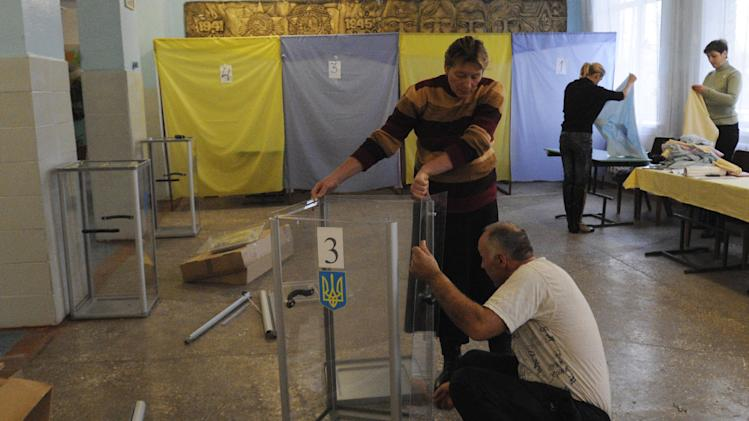 Workers prepare a polling station in the village of Bobryk, some 60 km (37 miles) north  of Kiev Ukraine, Saturday, Oct. 27, 2012.  Ukraine is scheduled to hold parliamentary elections on Oct. 28.(AP Photo/Sergei Chuzavkov)