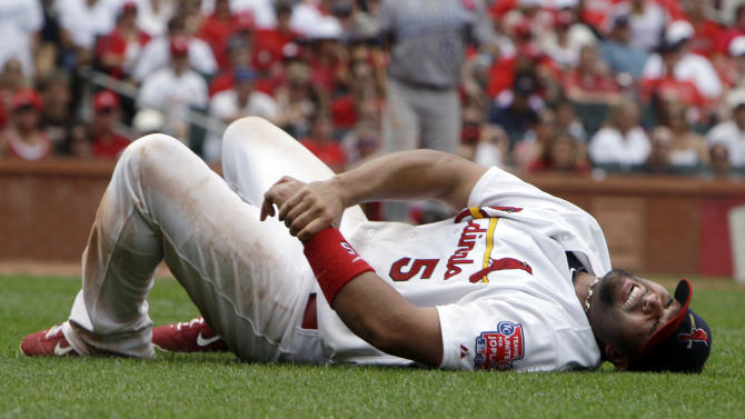 St. Louis Cardinals first baseman Albert Pujols grabs his left wrist after being injured on a play at first base during the sixth inning of an interleague baseball game against the Kansas City Royals Sunday, June 19, 2011, in St. Louis. Pujols left the game (AP Photo/Jeff Roberson)