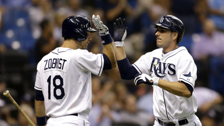 Tampa Bay Rays' Matt Joyce, right, gets a high-five from on-deck batter Ben Zobrist after scoring on a fifth-inning single by Evan Longoria off Oakland Athletics starting pitcher Tyson Ross during a baseball game Thursday, Aug. 23, 2012, in St Petersburg, Fla. (AP Photo/Chris O'Meara)