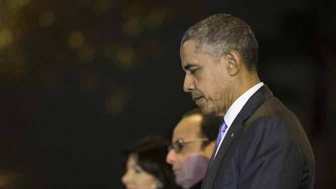 President Barack Obama, right, French President Francois Hollande, second from right, and Paris Mayor Anne Hidalgo pause for a moment of silence at the Bataclan, site of one of the Paris terrorists attacks, after Obama arrived in town for the COP21 climate change conference, on Monday, Nov. 30, 2015, in Paris. (AP Photo/Evan Vucci)