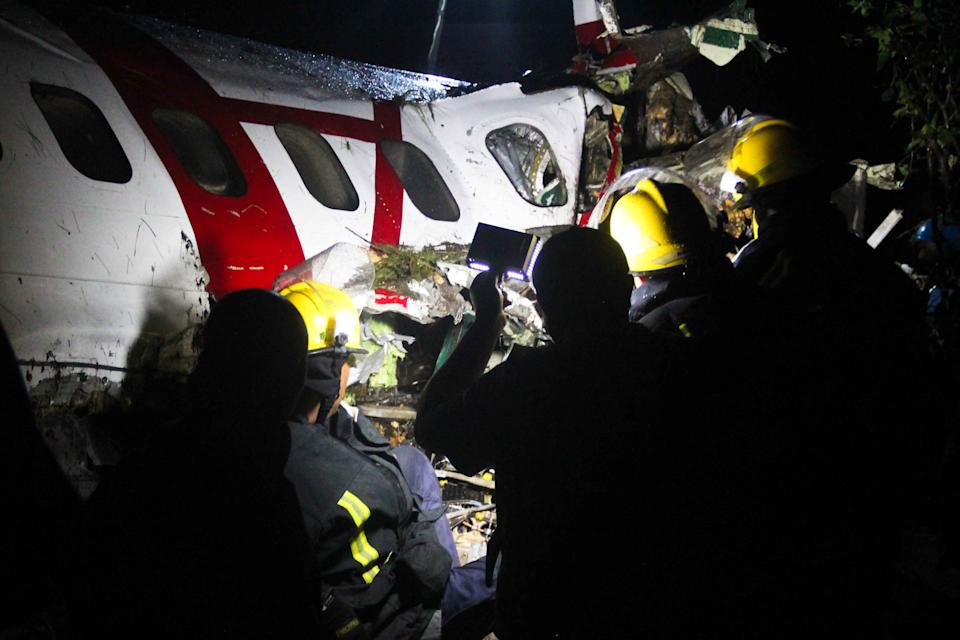 Rescue workers search the cabin of a plane that crashed in Goma, Congo Monday, March 4, 2013. A Fokker airplane of the private airline CAA crashed in the city center Monday, killing at least six people onboard. There were no reported casualties on the ground.(AP Photo/Melanie Gouby)