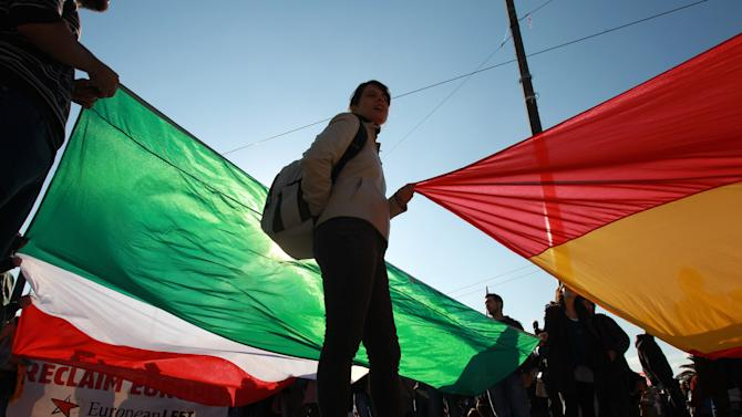 Protesters hold Spanish and Italian flags outside the Greek parliament during a protest in Athens, Wednesday, Nov. 14, 2012. Workers across the European Union sought to present a united front against rampant unemployment and government spending cuts Wednesday with a string of strikes and demonstrations across the region. (AP Photo/Thanassis Stavrakis)