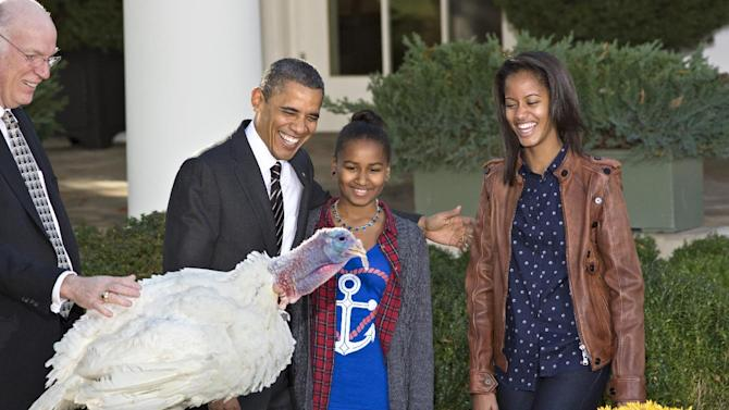 "President Barack Obama, with daughters Sasha, center, and Malia, right, carries on the Thanksgiving tradition of saving a turkey from the dinner table with a ""presidential pardon,"" at the White House in Washington, Wednesday, Nov. 21, 2012.  After the ceremony, ""Cobbler"" will head to George Washington's historic home in Virginia to be part of the ""Christmas at Mount Vernon"" exhibition. National Turkey Federation Chairman Steve Willardsen is at left. (AP Photo/J. Scott Applewhite)"