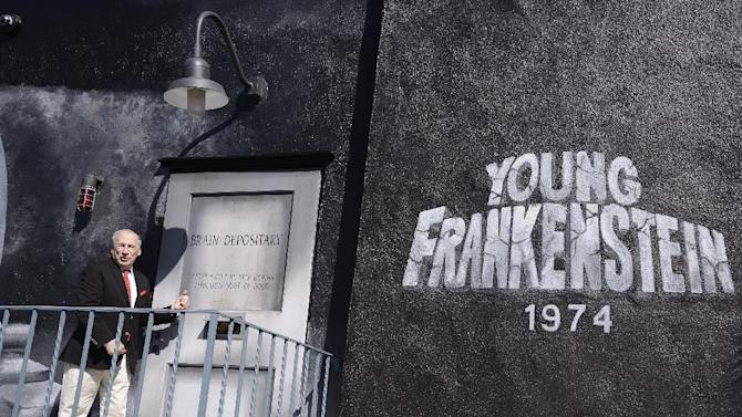 """IMAGE DISTRIBUTED FOR TWENTIETH CENTURY FOX HOME ENTERTAINMENT - Comedy legend Mel Brooks unveils """"Mel Brooks Boulevard"""" on the Fox Lot next to a mural tribute painted onto the side of Stage 5 where his feature film """"Young Frankenstein"""" was filmed over 40 years ago on Thursday, Oct. 23, 2014 in Los Angeles. The ceremony coincides with the """"Young Frankenstein"""" 40th Anniversary Blu-ray release. (Photo by Dan Steinberg/Invision for Twentieth Century Fox Home Entertainment/AP Images)"""