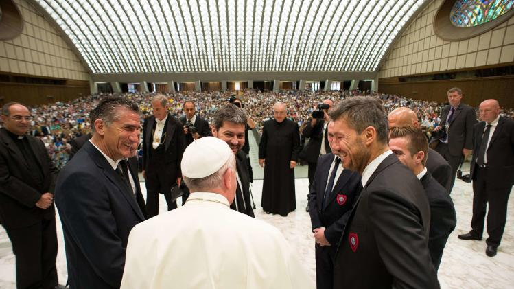 Pope Francis chats with representatives of Argentine soccer team San Lorenzo during a Wednesday general audience at the Paul VI hall at the Vatican