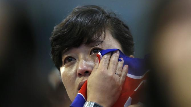A North Korean spectator wipes her eyes with the North Korean flag after seeing North Korea's Kim Unguk arrive at the men's 62kg weightlifting competition at the Moonlight Garden Venue during the 17th Asian Games in Incheon