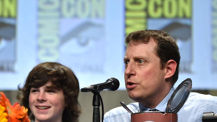 "Chandler Riggs, left, and executive producer Scott M. Gimple speak on stage at AMC's ""The Walking Dead"" panel on Day 2 of Comic-Con International on Friday, July 25, 2014, in San Diego. (Photo by John Shearer/Invision for AMC/AP Images)"